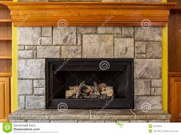 natural gas insert fireplace with stone and wood stock image natural gas insert fireplace with stone and wood stock image
