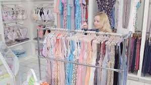 maternity store woman shopping for pregnancy clothes in baby and maternity shop
