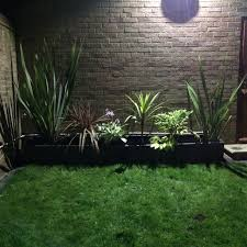 modern small low maintenance garden fake grass grey raised beds