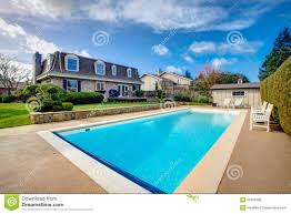 large backyard with flowerbed and swimming pool stock photo
