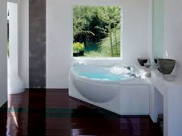 white corner bathtub on brown wooden floor plus square windows on