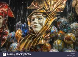 gold carnival mask surrounded by venetian glass ornaments