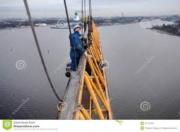 installers working jib fixed to the mast of tower crane editorial