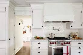 white subway tile kitchen white glazed cabinets installed with gas range and water pot filler