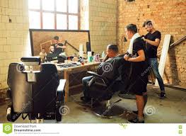 young guys making haircuts in the hipster style barber shop with