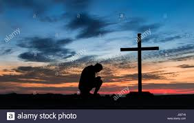 sunset a praying to a cross on a hill stock photo