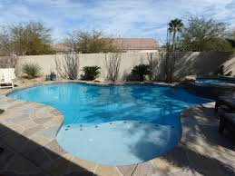 curvy backyard pool spa with stained concrete deck free form