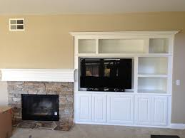 white wooden shelves next to grey stone fireplace connected by