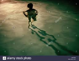 a young woman standing in a swimming pool at night silhouette