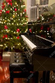 baby grand piano with tree presents in background