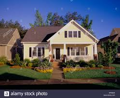 house with a porch small two story yellow house with black shutters a porch and brick