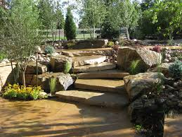 rustic flagstone patio with slab stairs and large boulders in