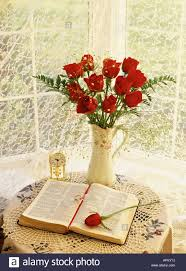 pitcher of roses dozen roses in pitcher anniversary clock and open bible stock