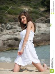 portrait of a teen with white dress at the beach stock photo