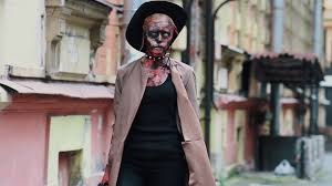 cosplayer in scary halloween costume of ghoul in cowboy hat from