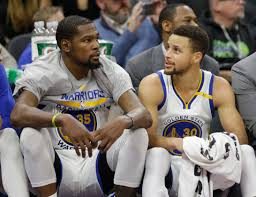 basketball player on bench 2 golden state warriors players 2 cleveland cavaliers players to