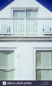 symmetrical view of part of white painted two storey house or