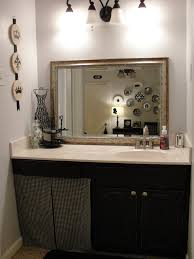 black wooden bathroom vanity with white top added by brown mirror