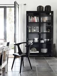 modern dining room with a black china cabinet containing books