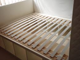 queen size bed frame which is having white painted mahogany wood