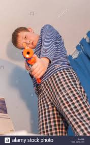 nerf bedroom a nine year old boy with a nerf gun in his bedroom stock photo