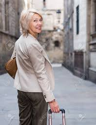 elegant mature woman elegant mature woman is posing with suitcase in time walking stock