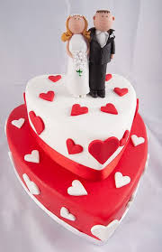 3 Tier Heart Shaped Wedding Cake With Pink Frosting And Red Roses