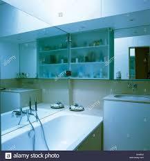 mirror above bath and washbasin in modern bathroom with down
