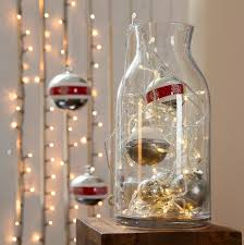 glass vase filled with lights and ornaments