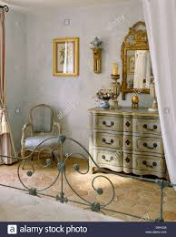 wrought iron bed in pale gray french country bedroom with ornate