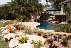 custom swimming pool with natural stone waterfalls and pool grotto