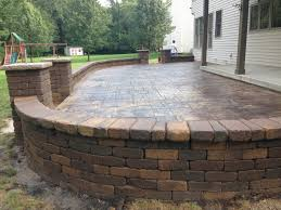 decorative stamped concrete patio with retaining wall and pillars