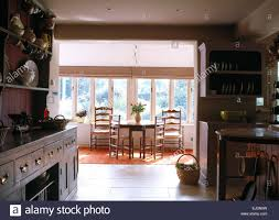 open plan country kitchen and dining room with antique ladder back