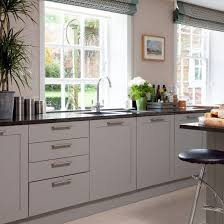grey kitchen cupboards with black worktop kitchen with pale wood floor soft grey units black granite