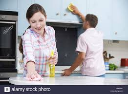 couple cleaning kitchen surfaces and cupboards together stock
