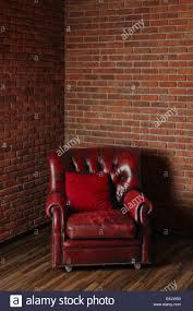 old dark red leather armchair in the corner of the room with brick