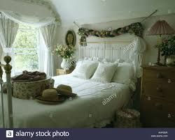 fabric garland above white wrought iron and brass bed with hatbox