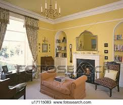 yellow livingroom stock photo of chaiselongue in front of fireplace in yellow