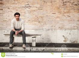 handsome young man sitting on marble bench with bricks background