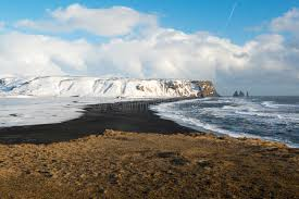 winter landscape with mountains black sand beach and ocean waves