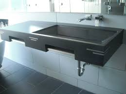 rectangle black concrete sink and steel faucet on white tiles