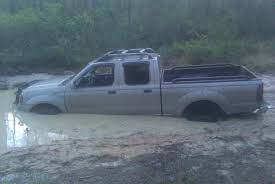 white jeep stuck in mud your