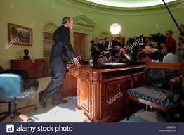 u s president george w bush standing behind the resolute desk
