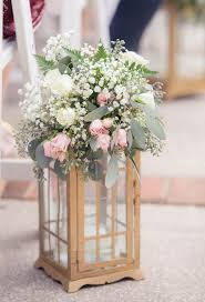 white ivory and light pink centerpiece flowers in gold lantern