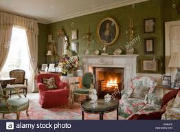 comfortable armchairs around fireplace with lit fire in country