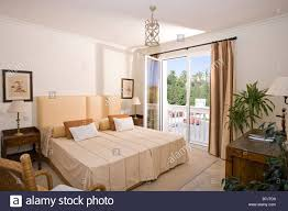 bed with cream bedlinen in comfortable bedroom in spanish holiday
