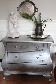 using silver spray paint with furniture wax redecorating the silver painted bombe chest