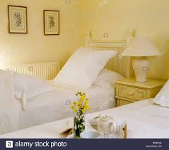 cream lamp on table between twin beds with white pillows and