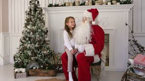 cute little singing a christmas song sitting on santa claus