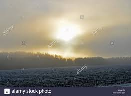 sun shining through clouds and fog location aura finland stock